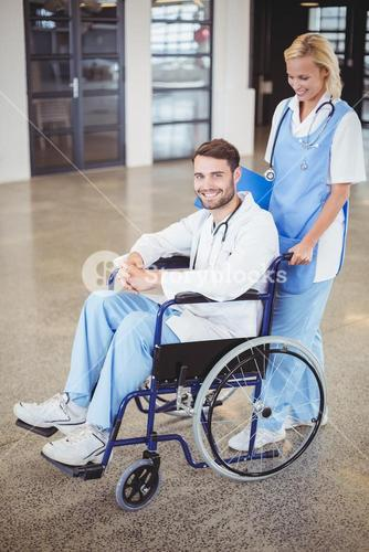 Portrait of smiling doctor sitting on wheelchair with female colleague