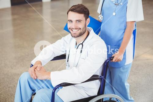 Portrait of smiling doctor sitting on wheelchair with colleague
