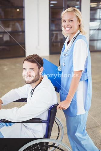 Portrait of smiling doctor on wheelchair with female colleague