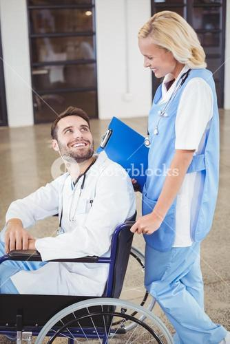Smiling doctor on wheelchair interacting with female colleague