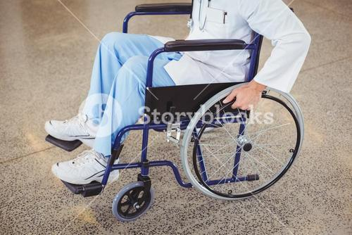 Midsection of doctor sitting on wheelchair
