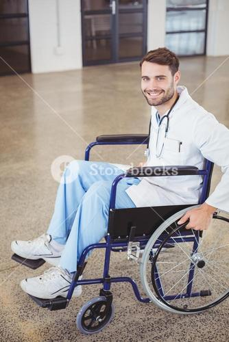 Portrait of happy doctor sitting on wheelchair