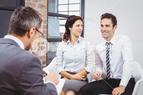 Business professional discussing with smiling clients