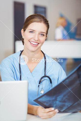 Portrait of smiling female doctor holding X-ray