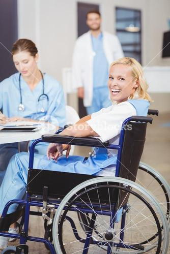 Portrait of cheerful female doctor sitting on wheelchair