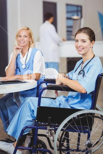 Portrait of smiling doctor sitting on wheelchair with colleagues