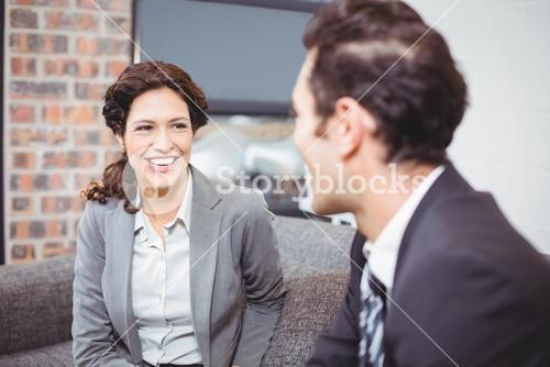 Cheerful business professionals sitting on sofa