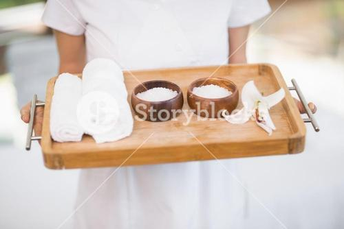 Female masseur holding tray with spa therapy products