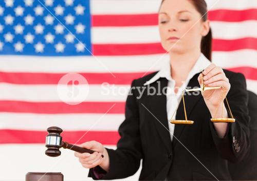 Close up of a young judge knocking a gavel and holding scales of justice
