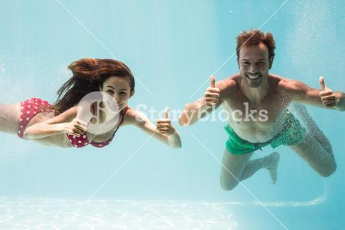 Smiling couple showing thumbs up while swimming