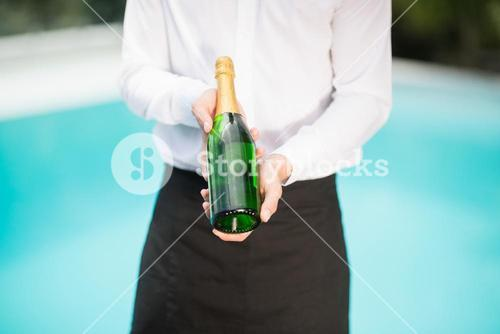 Midsection of waiter holding champagne bottle