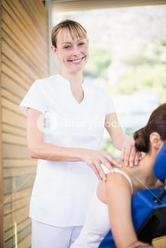 Portrait of happy physiotherapist giving shoulder massage