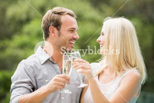 Smiling couple toasting champagne flutes