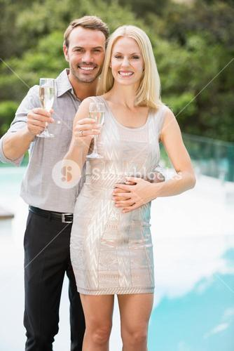 Smiling couple showing champagne flutes