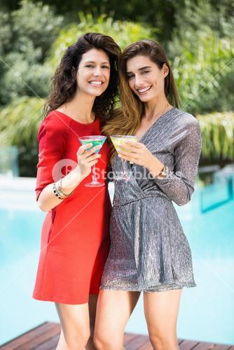 Gorgeous female friends by swimming pool