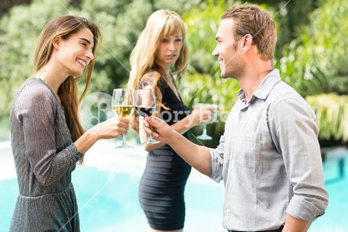 Jealous woman looking at happy couple toasting wine