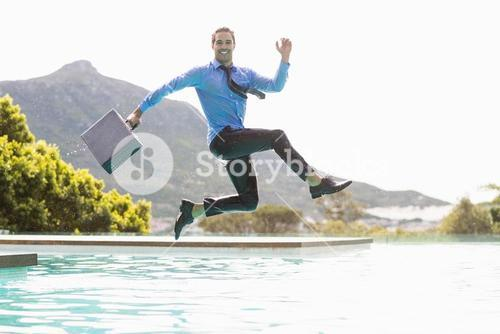 Businessman jumping over swimming pool