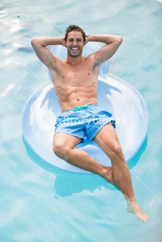 Happy shirtless man relaxing on inflatable ring
