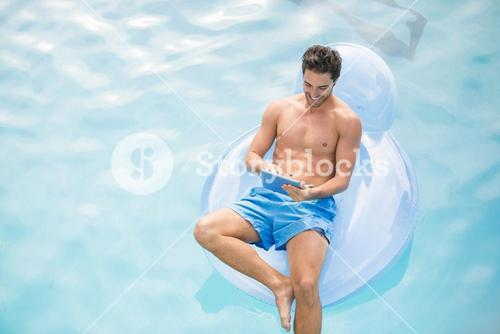 Man using digital tablet on inflatable ring