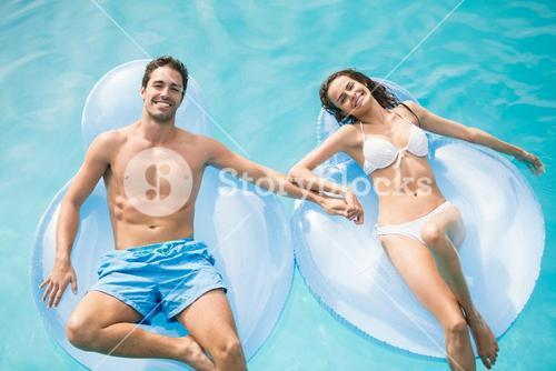 Happy couple relaxing on inflatable ring