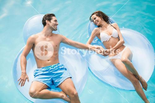 Happy young couple relaxing on inflatable ring