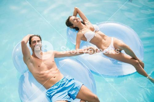 Couple smiling while relaxing on inflatable ring