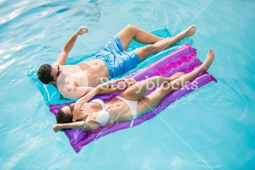 Couple relaxing on inflatable raft