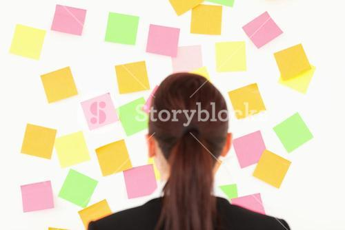 Redhaired woman looking at a wall full of repositional notes