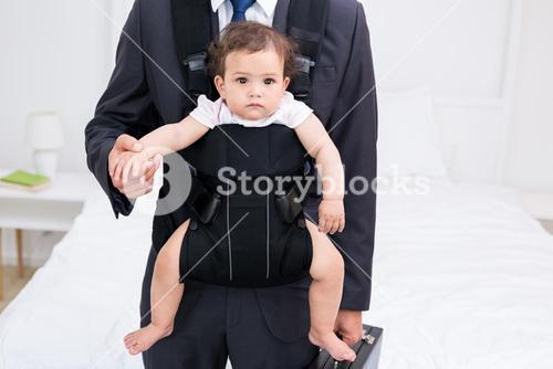 Midsection of father carrying baby and briefcase