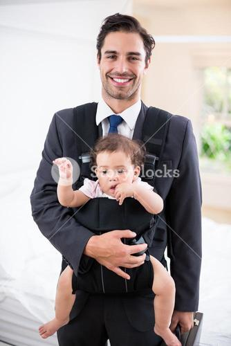 Portrait of smiling father carrying baby