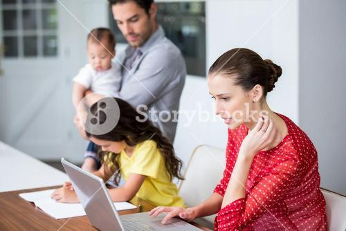 Mother working on laptop with daughter studying