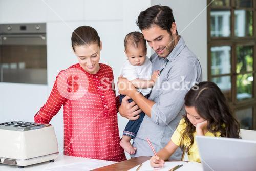 Smiling family with daughter studying at desk
