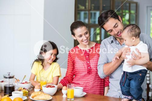 Smiling family at breakfast table