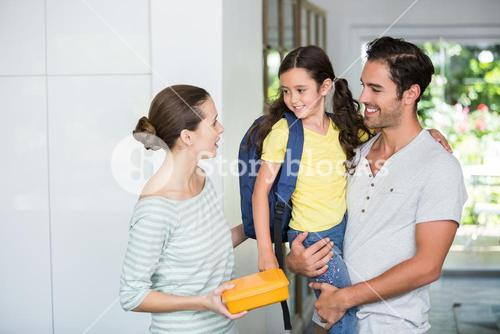Mother holding lunch box with father carrying daughter