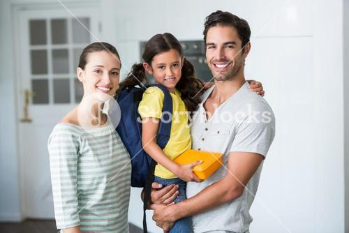 Portrait of happy family with daughter holding lunch box