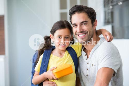 Portrait of smiling father and daughter with lunch box