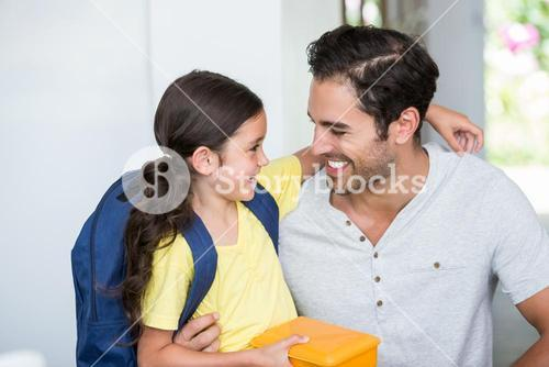 Smiling father and daughter with lunch box