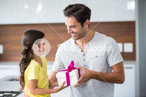 Smiling daughter giving gift box to father