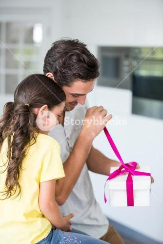 Father opening gift given by daughter