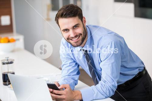 Businessman using mobile phone at home