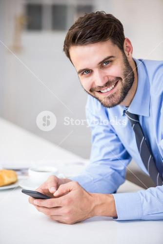 Young businessman using mobile phone at home