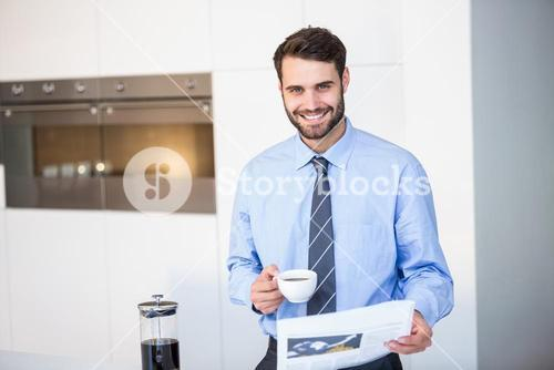 Portrait of businessman reading newspaper while drinking coffee by table at home