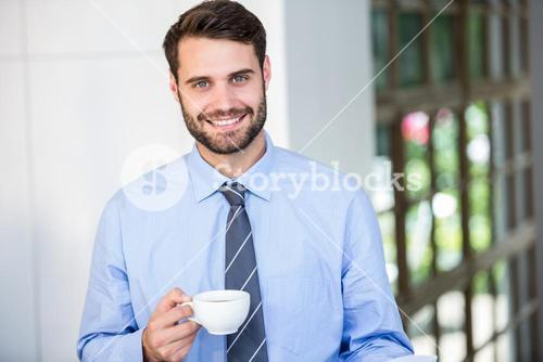 Confident businessman holding coffee cup