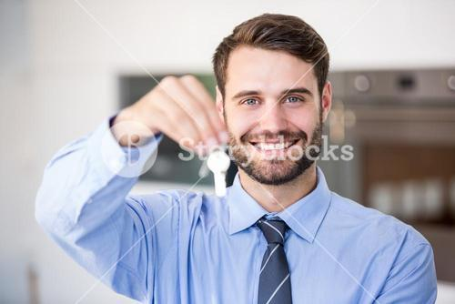 Happy businessman showing house keys