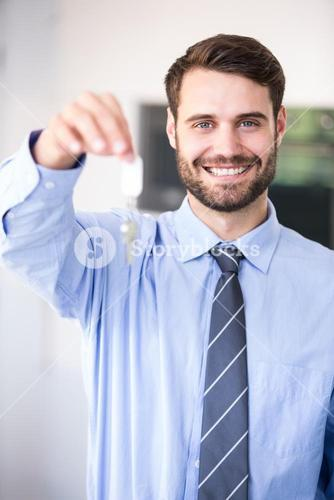 Businessman smiling while showing house keys