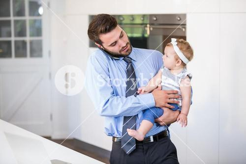 Businessman talking on cellphone while carrying daughter
