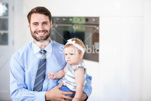 Happy businessman carrying daughter