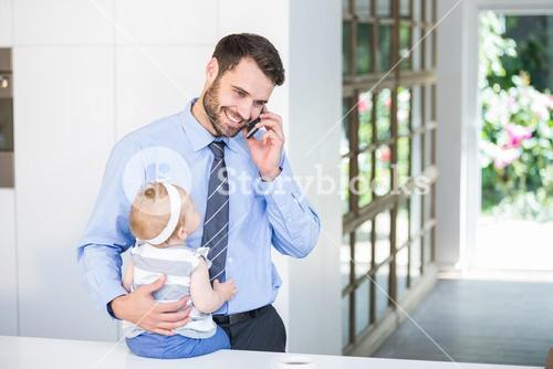 Businessman talking on cellphone while holding daughter