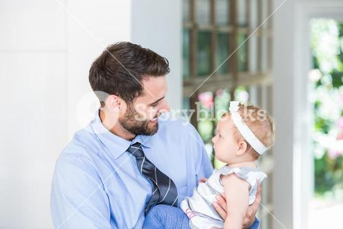 Cheerful businessman carrying daughter