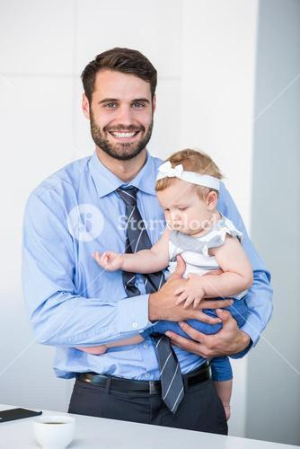 Cheerful businessman carrying daughter by table